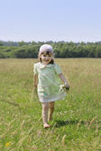 Little barefoot girl with flowers runs among grass of meadow at — Stock Photo