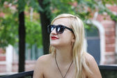 Beautiful girl in sunglasses looks away in park at summer day — Stock Photo