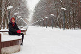 Beautiful girl in black sits on bench outdoor at winter day in p — Stock Photo