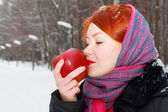 Pretty girl in red kerchief holds big red apple outdoor at winte — Stock Photo