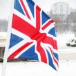 Flag of United Kingdom on wind at winter cloudy day in street of — Stock Photo #42034075