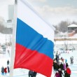Flag of Russia on wind at winter cloudy day in street of city — Stock Photo