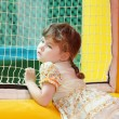 Stock Photo: Little beautiful girl in dress stands in yellow bouncy castle an