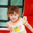 Stock Photo: Little pretty happy girl in dress plays in red bouncy castle