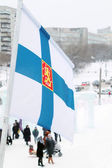 Flag of Finland on wind at winter cloudy day in street of city — Stock Photo