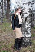 Mladá žena stojí v lese vedle velké břízy a úsměvy — Stock fotografie