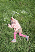 Happy pretty little girl in pink lies on green grass at spring d — Stock Photo