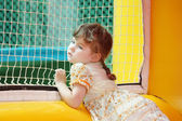 Little beautiful girl in dress stands in yellow bouncy castle an — Stock Photo