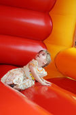 Little beautiful happy girl lies in red bouncy castle and looks  — Stock Photo