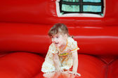 Little pretty happy girl in dress plays in red bouncy castle and — Stock Photo