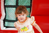 Little pretty happy girl in dress plays in red bouncy castle  — Stock Photo