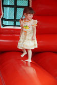 Little beautiful happy girl jumps on red bouncy castle and laugh — Stock Photo