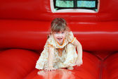 Little beautiful girl in dress plays in red bouncy castle and sh — Stock Photo