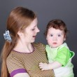 Portrait of happy young mother with cute baby in her arms. Focus on boy — Stock Photo #49874013