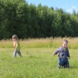 Little boy and girl walk on grass at green meadow in sunny day — Stock Photo #49874541