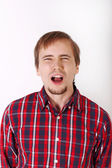 Young man with beard in checkered red shirt shouts — Stock Photo