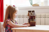 Pretty little girl sits at table with small wooden toy house and — Stock Photo