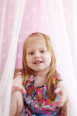Pretty little girl sits among transparent curtains and stretches — Stock Photo