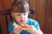 Little girl in blue dress with big appetite eating red ripe watermelon — Stok fotoğraf