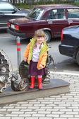 PERM, RUSSIA - JUL 18, 2013: Little girl near city sculpture Parade of Planets near Crystal cinema — Stock Photo