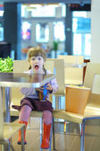 Little girl with open mouth sitting at table in cafe with popcorn — Stock Photo