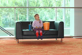 Little girl sitting on black sofa with popcorn and soda — Stock Photo
