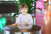 Cute little girl moves her hands over round table in cafe — Stock Photo