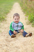 Little handsome happy boy sits in sawdust in summer day — Stock Photo