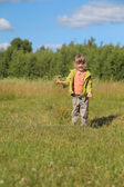 Little beautiful girl overspreads sawdust at grass of green mead — Stock Photo