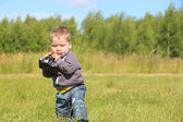 Little handsome boy holds camera and walks at meadow in summer d — Stock Photo