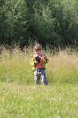 Little pretty girl stands on green grass and holds camera at sum — Foto de Stock