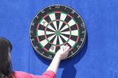 Woman removes darts from dartboard on blue wall at sunny day — Stock Photo