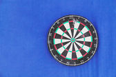 Round dartboard with numbers and with javelins on blue wall  — Stock Photo