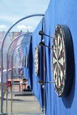 Dartboard with javelins on blue wall on street in summer day — Stock Photo