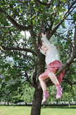 Happy little cute girl sits on tree branch in park at summer day — Foto de Stock