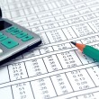 Stock Photo: Numbers on paper and calculator