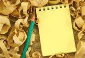Notebook on wooden background shavings — Zdjęcie stockowe