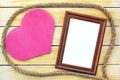 Heart and photo frame on the background of wooden boards — Stock Photo