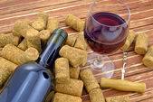 Glass of wine on background of bottle and corks — Stock Photo