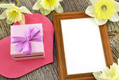 Gift box with photo frame on the background of wooden board — Stock Photo