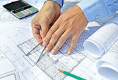 Hands with tool and project drawings — Stock Photo