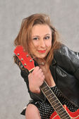 Funny girl with red guitar — Stock Photo