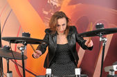 Young woman in dress with polka dots and jacket playing drums — ストック写真
