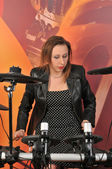 Young woman in dress with polka dots and jacket playing drums — Stock Photo