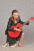 Emotional girl with a red guitar, on a grey background — Stock fotografie