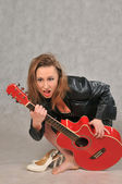 Emotional girl with a red guitar, on a grey background — Stock Photo