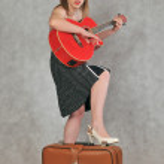 Веселая девушка с красной гитарой и ретро-чемоданом — Stock Photo