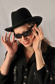 Portrait of a beautiful girl with sunglasses and a hat — Stock fotografie