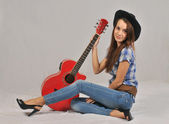 Young girl standing in a blouse with short sleeves, his right hand on the neck of the red guitar , and the left is based on a stretched forward with the right leg — Stock Photo