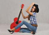 Young girl sitting in a blouse with short sleeves, his right hand on the neck of the red guitar , and his left hand on the head of a black hat — Stock Photo